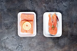 two fresh raw salmon steaks are laying on white food tray made from polystyrene foam
