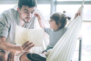 Dad and daughter read a book