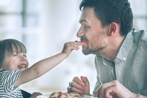 Dad and daughter eat pizza