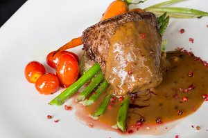 grilled beef steaks with spices,tomato and asparagus in pink peper sauce