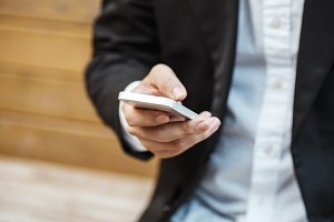 Close-up smart Business man wearing modern black suit and white shirt and texting on mobile smart phone.