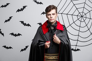Vampire Halloween Concept - Portrait of handsome caucasian Vampire in black and red halloween costume.