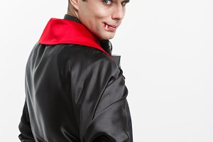 Vampire Halloween Concept - Portrait of back view handsome caucasian Vampire in black and red halloween costume.