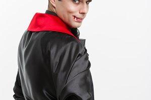 Vampire Halloween Concept - Portrait of back view handsome caucasian Vampire in black and red halloween costume.
