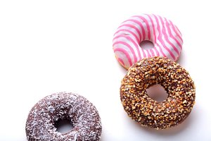 Assorted doughnuts in the glaze, colorful sprinkles and nuts on a white background.