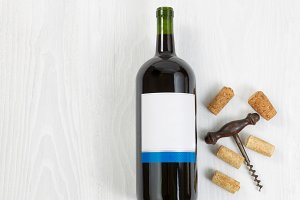 Red wine bottle on white wood