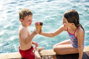 Kids toast with ice creams at pool