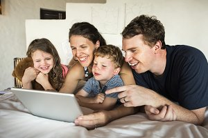 Family using a laptop in bed