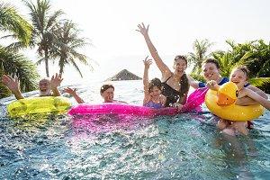 family enjoy the summertime in pool