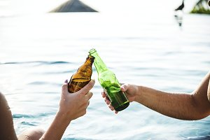 Young couple having beer by the pool