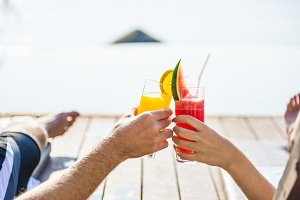 Couple toast with cocktails by pool