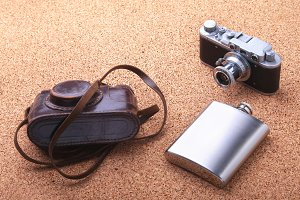 Gadgets and accessories for men on light wooden background. Fashionable men s lighter, Stainless hip flask and retro camera.