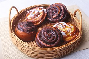 Freshly baked homemade sweet bun or sweet rolls with cinnamon in a wicker basket.