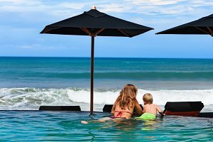 Mother with son in infinity pool