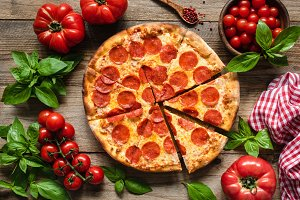 Pepperoni pizza, tomatoes and basil