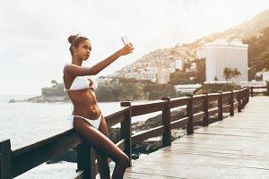Black girl taking selfie on a beach