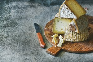 Cheese assortment on wooden board, copy space