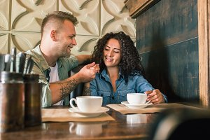 Happy young couple is drinking coffee and smiling while sitting at the cafe