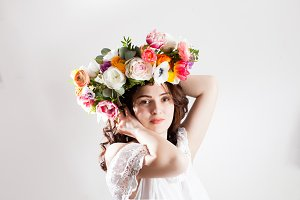 Woman holds her head with art flowers