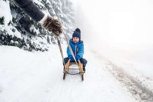 Mother pulling son on sledge. Foggy white winter nature.