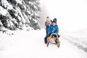 Mother pushing son on sledge. Foggy white winter nature.