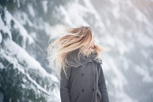 Beautiful young woman on a walk in winter nature