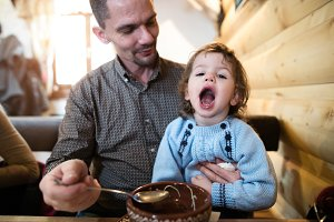 Father feeding his son with soup. Boy with mouth open.