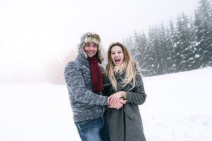 Beautiful young couple in love on a walk, winter nature