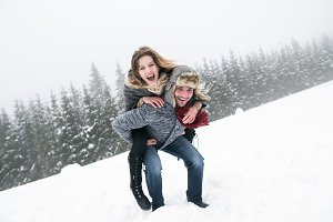 Couple in love, man giving woman piggyback. Winter nature.