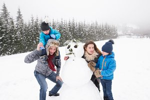 Parents with their sons, playing in the snow, building snowman.