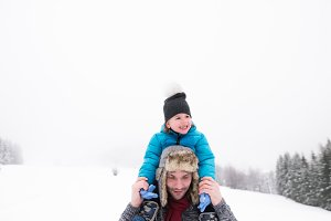 Father giving his son piggyback. Winter nature.