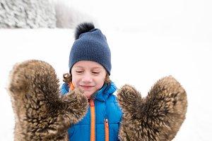 Cute boy wearing big furry gloves outside in winter nature