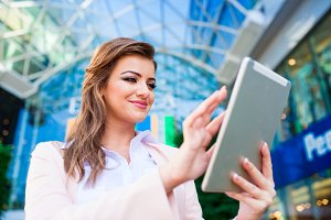 Businesswoman working on tablet against glassy modern office bui