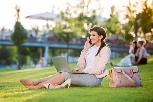 Businesswoman sitting in park checking her smartphone, sunny sum