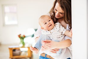 Portrait of a young mother with a baby son at home. Copy space.