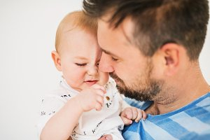 Portrait of a young father with a baby son at home. Close up.