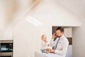 Father with shirt and tie and smartphone feeding a baby son at home, when talking on the phone.