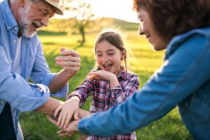 A small girl with her senior grandparents having fun outside in nature at sunset.