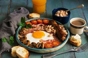 A traditional full English breakfast with fried egg, sausage, mushrooms, beans, bacon and tomatoes on a rustic wooden green table.