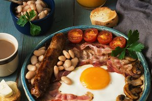 Full English breakfast with scrambled eggs, sausage, mushrooms, beans and bacon on a wooden rustic green table.Toast with butter, coffee and orange juice.