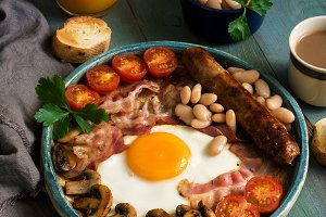 Full English breakfast with scrambled eggs, sausage, mushrooms, beans and bacon on a wooden rustic green table.