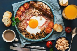 Traditional English breakfast. Fried egg with sausage, mushrooms, beans, tomatoes and bacon. View from above.Toast with butter, coffee and orange juice.