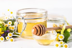 Honey  in a jar with wild herbs on white