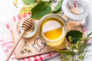 Honey  in a jar with dipper on white