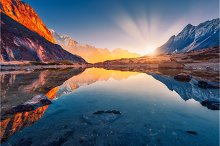 Mountains with illuminated peaks, stones in mountain lake at sun by  in Nature