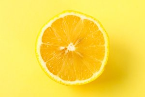 Top view of a one orange fruit slice on bright background in pastel color.