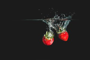 Red strawberry dropping in water