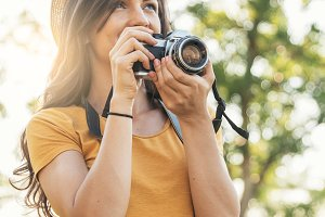Smiling young woman taking photos