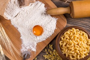Eggs and pasta on wooden board
