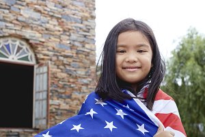 Cute little girl with USA flag in park